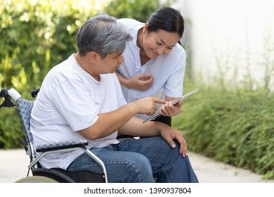 An elderly male patient sitting on a wheelchair while choosing a health care package from a tablet with his wife. They expect to return to normal. Health care concept.