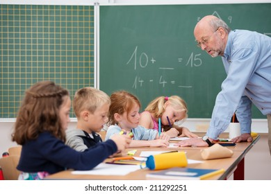 Elderly male teacher in primary school leaning over a long desk chatting to a group of young boys and girls with the blackboard in the background