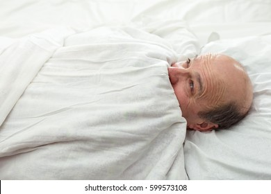 An elderly man is afraid of the dark and hides under a blanket. Problems with sleeping in old age.
