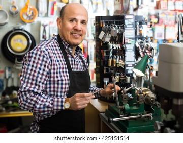 Elderly man in apron working in locksmith and making duplicates of keys