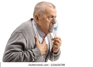 Elderly man with asthma using an inhaler and holding his chest isolated on white background