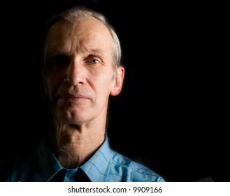 elderly man, background is black. Side light.