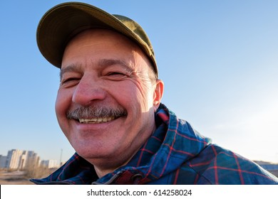 An elderly man in  baseball cap looks  and smiles. Positive mood for a walk
