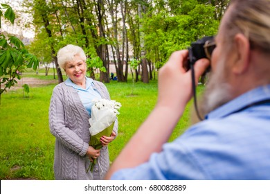 An elderly man with a beard is making a photo of a wife with flowers in a green park