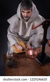 An elderly man with a beard in monastic clothing writes a scientific work in a dark room.