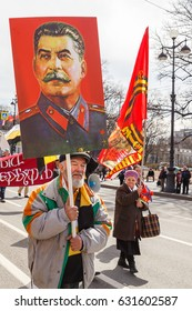 An elderly man bears a portrait of the leader of the Soviet Union Joseph Stalin during the May holidays in May 1, 2017 in St. Petersburg, Russia