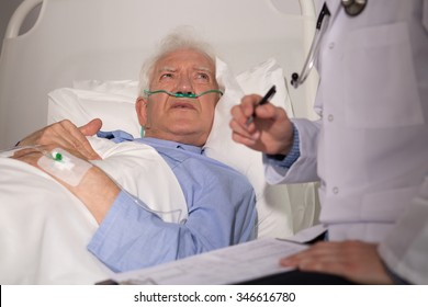Elderly man in bed examined by doctor