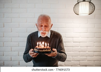 Elderly man blowing out birthday candles