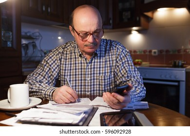 An elderly man  calculates the family budget at night. Trying to find a way out of financial problems
