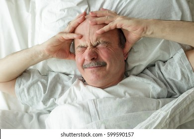 An elderly man can not fall asleep from loud noise and headaches. He holds his hands at the head, closes his ears with his fingers and frowns.