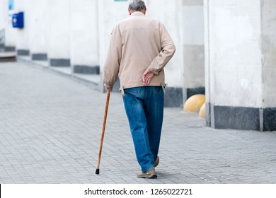 an elderly man with a cane in his left hand walks along the street and holds his right hand behind a sore back