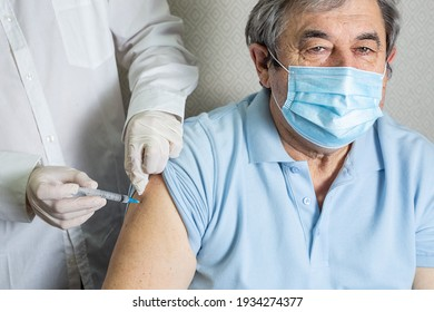 An elderly man of Caucasian appearance in a mask receives a dose of coronavirus vaccination at home, the doctor came to the patient to give a protective injection against the disease