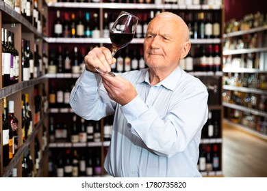 Elderly man checks the color and taste of red wine in a liquor store
