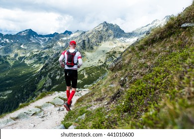 elderly man in compress socks running ultra race on the trail with epic view on high mountain peaks