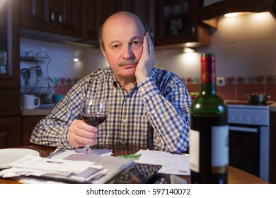 An elderly man considers a family budget and tiredly drinks red wine, trying to relax
