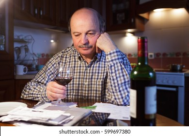 An elderly man considers a family budget and tiredly drinks red wine, trying to relax.