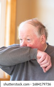 Elderly man coughing into his elbow to avoid spreading virus, germs and air born droplets amid coronavirus, Covid-19.
