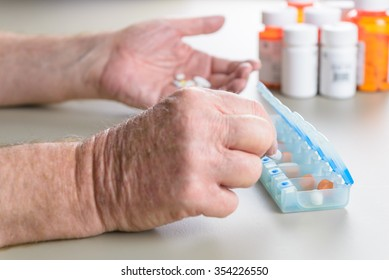 Elderly man counts out his pills and medication for the week using a daily pill box.