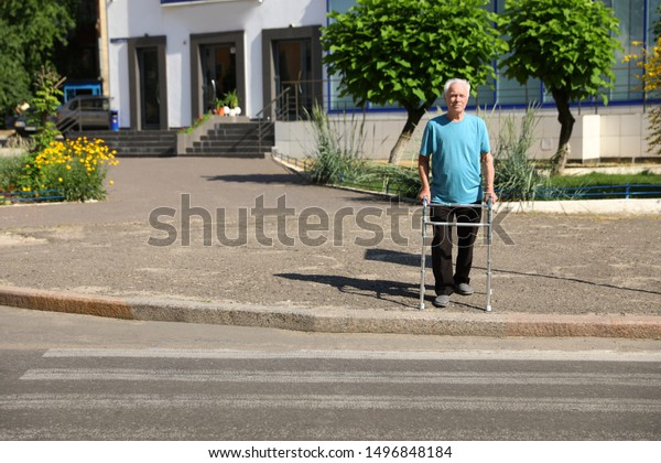 Elderly man crossing street with walking frame. Space for text