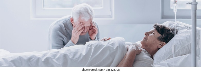 Elderly man crying and mourning the loss of his wife, sitting by her side in the hospital