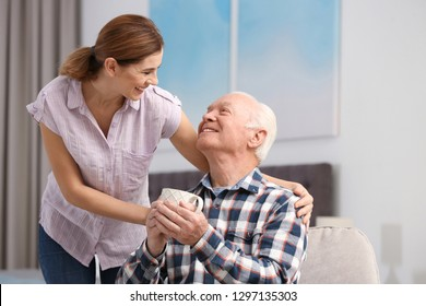 Elderly man with cup of tea near female caregiver at home. Space for text