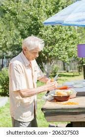 The elderly man cut vegetables for dinner in sunny day