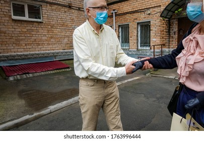Elderly man in disposable mask receives birthday present from a female friend wearing mask and gloves outside an apartment building. Social distancing in the time of coronavirus