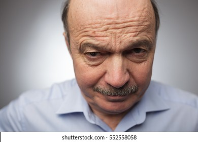 Elderly man dissatisfied frowns and looks sullenly. Wrinkles on the forehead of negative events