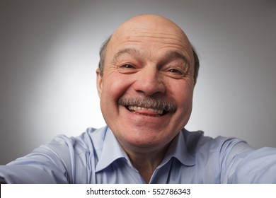 Elderly man doing selfie and shows his tongue. Fooling around on camera, to stay in a good mood