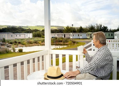 Elderly man drinking a mug of coffee sitting on the veranda of a luxury static caravan in North Wales taking in the scenic views of the Welsh  Countryside.