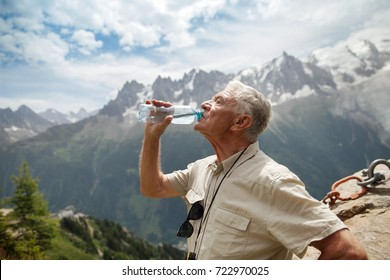 elderly man drinking water from bottle in the mountains
