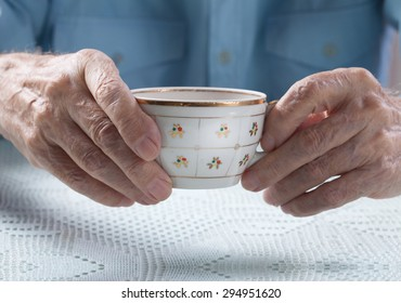 An elderly man drinks tea at home. Senior man holding cup of tea in their hands at table close-up
