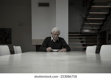 Elderly man eating dinner completely alone in huge house