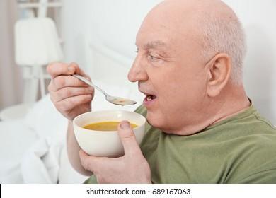 Elderly man eating soup in bed