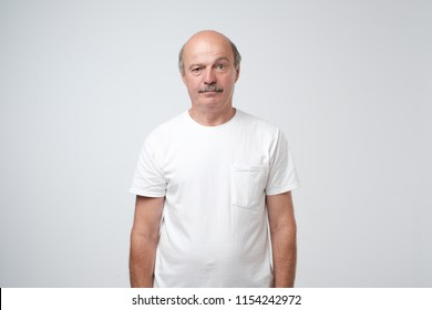 Elderly man emotions, portrait of serious senior caucasian man in white t-shirt looking at camera against gray wall
