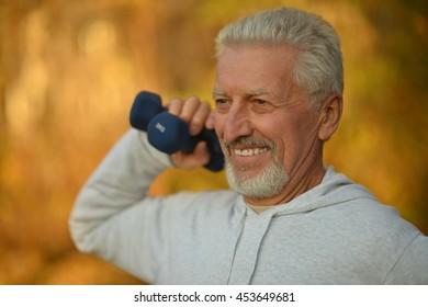 Elderly man exercising with dumbbells