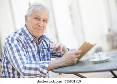 Elderly man with eyeglasses reading book outside