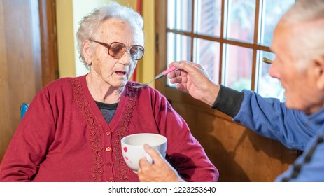 Elderly man feeding his wife at home, focus on the woman.