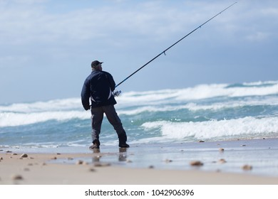 Elderly man fishing with a fishing rod on the beach in Acre, Israel