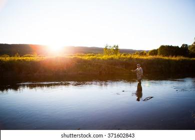 Elderly man fly fishing in a river