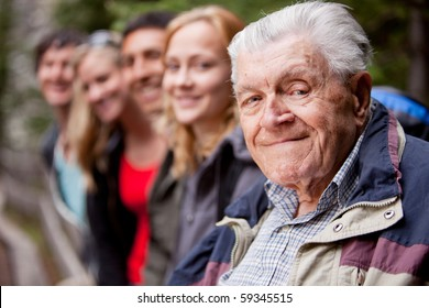An elderly man in front of a group of young people