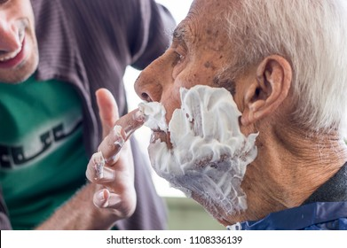 Elderly man getting his beard shaved by young skilled man at home. Man applying shaving foam to old man's face.