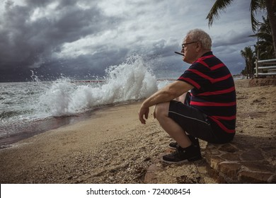 Elderly man in glasses and a striped t-shirt sitting on the beach and looking at the storm smokes a cigar. A wise man in age, the theme of loneliness.