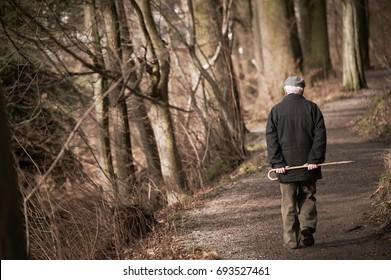 Elderly man going away in park. Toned