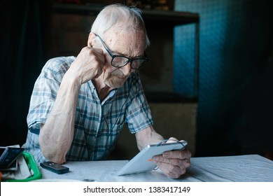 Elderly man grandfather reading from tablet at home