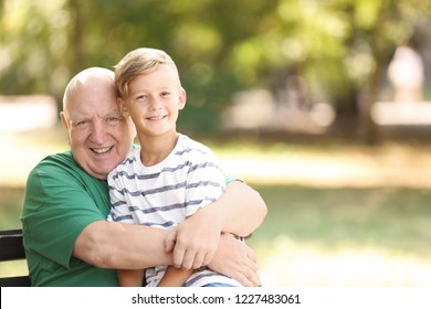 Elderly man with grandson on bench in park
