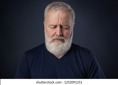 Elderly man with gray beard looking down and thinking