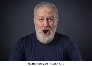 An elderly man with a gray beard with a very surprised mimic