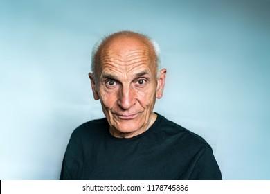 An elderly man with gray hair, piercing looks ahead