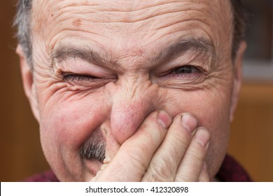 Elderly man hands nose plugs because of unpleasant smell